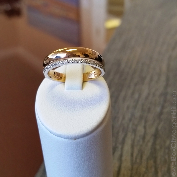 two tone elegant wedding ring for bride with solid yellow gold band and attached white gold prong set eternity ring on table top