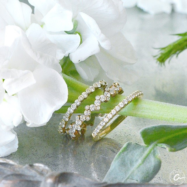 stackable yellow gold and diamond eternity wedding bands and anniversary rings on stem of white flowers in floral bouquet