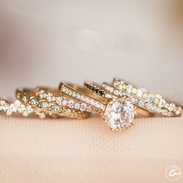 yellow gold diamond double prong engagement ring shown with six diamond eternity wedding bands styles on fabric