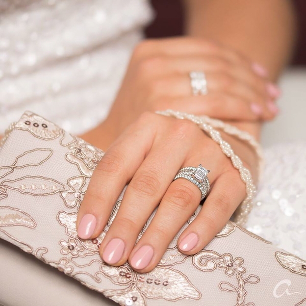 bride on wedding day wearing two white gold and diamond wedding bands that could also be worn as anniversary bands