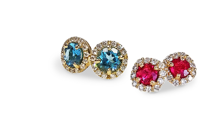 one pair each of diamond halo pierced stud earrings with prong set ruby and blue topaz gemstones in the center of design