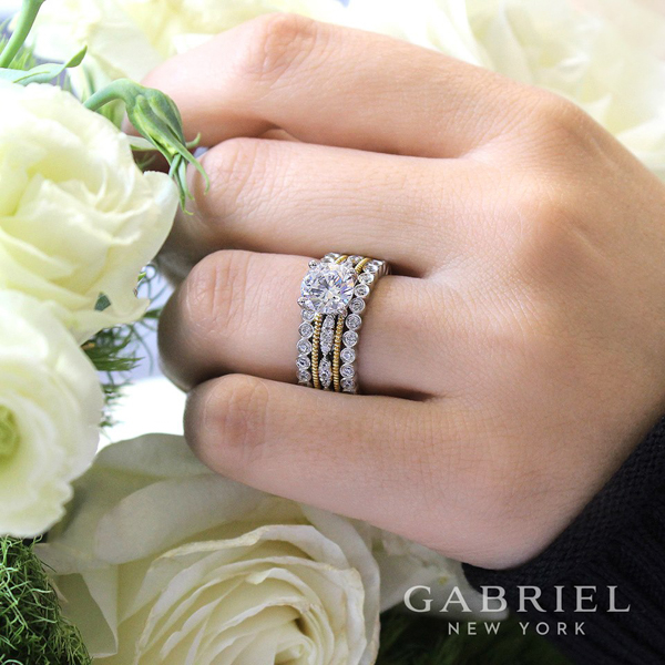 sparkling stackable diamond wedding rings and anniversary bands with a diamond engagement ring next to a beautiful flowers