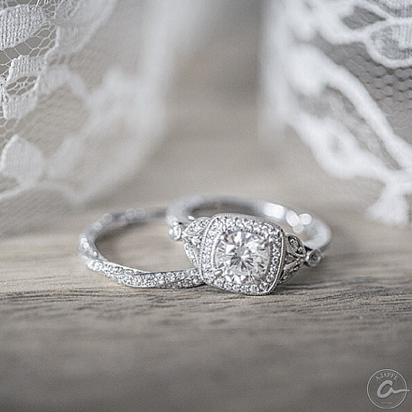 white gold wedding ring with twisted eternity band design and engagement ring with round diamond in vintage halo setting