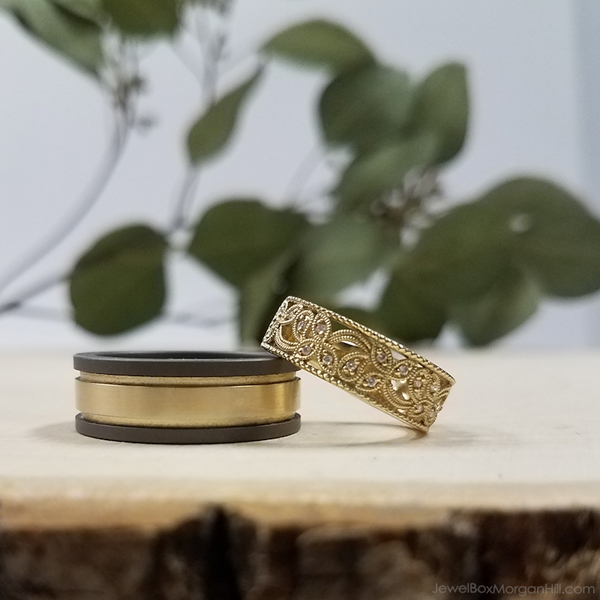 his and hers wedding bands showing mens gold and black wedding band and womens gold diamond band with filigree detail