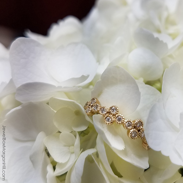 close up of yellow gold bezel set diamond eternity wedding ring with beaded metal detail nestled in white floral arrangement