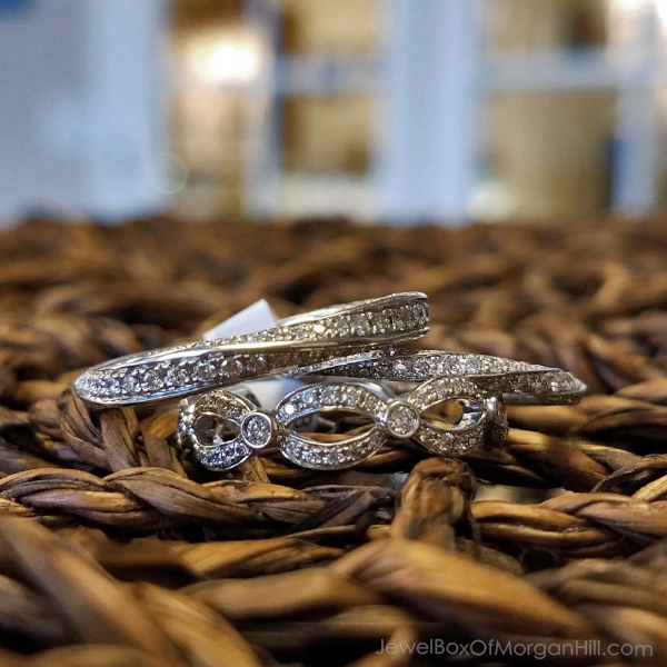 close up of two white gold and diamond wedding rings on brown basket at wedding venue one design is twisted like a mobius strip